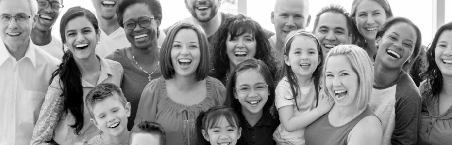 A multi-ethnic family group standing together happily while smiling and looking at the camera.
